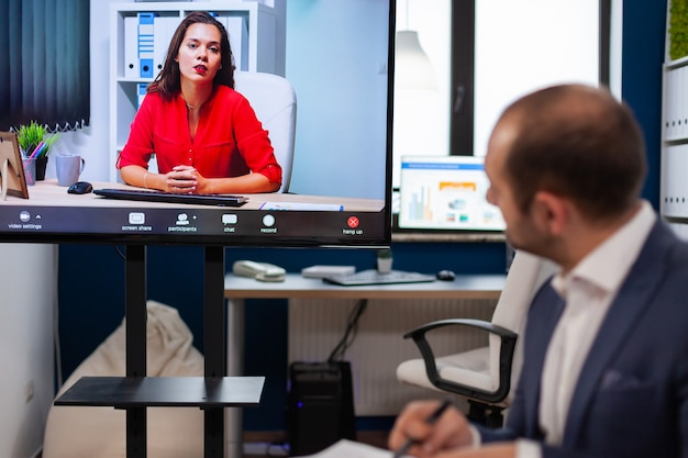 Executive manager discussing with remote colleagues on video call sitting in business office business people talking to webcam, do online conference participate internet brainstorming, distance office