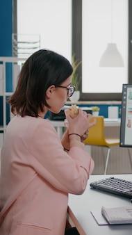 職場のデスクでマーケティング戦略を分析しながら、おいしいサンドイッチを食べるエグゼクティブマネージャー。テイクアウトオーダーの出前宅配、ランチミールブレイクパッケージをスタートアップオフィスでお届けします。