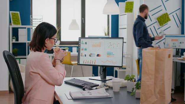 Исполнительный менеджер ест вкусный бутерброд, анализируя маркетинговую стратегию за столом на рабочем месте