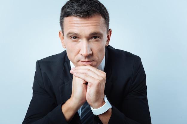 エグゼクティブマネージャー。彼のあごを持って、彼の仕事について考えている間あなたを見ている素晴らしい成功したハンサムなマネージャー