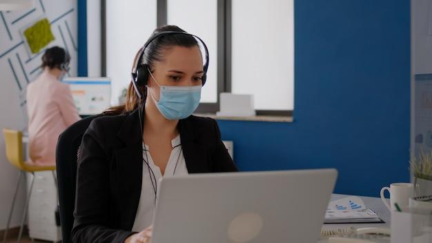 보호용 안면 마스크와 헤드폰을 쓴 경영진은 비즈니스 프로젝트에서 일하는 팀과 마이크에 대고 이야기합니다. 코로나바이러스 전염병 동안 새로운 일반 사무실에 앉아 있는 사업가
