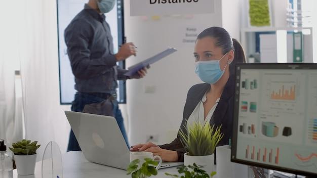 会社のオフィスの机のテーブルに座っている間、ラップトップコンピューターでマーケティング情報を入力するフェイスマスクを持つエグゼクティブマネージャー。 covid19による感染を避けるために社会的距離を尊重するチーム