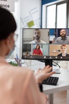 Executive manager with medical face mask discussing management statistics with remote team having online videocall meeting conference on laptop working in startup office. teleconference on screen