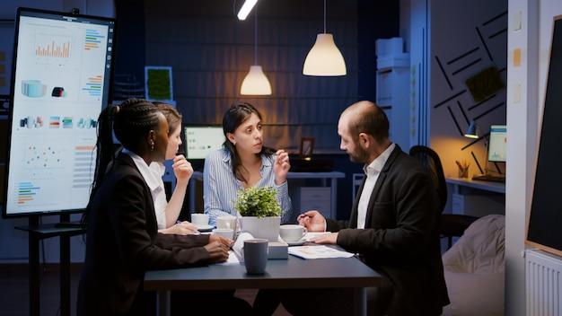 オフィスの会議室で残業中の会社の戦略で働く経営統計を説明するエグゼクティブマネージャーの女性