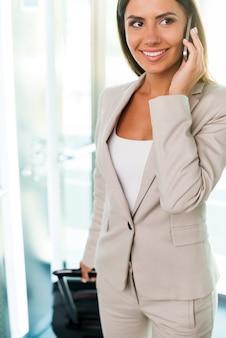 이동 중입니다. 정장 차림의 아름다운 젊은 여성 사업가가 휴대전화로 통화하고 엘리베이터에서 내리면서 웃고 있다