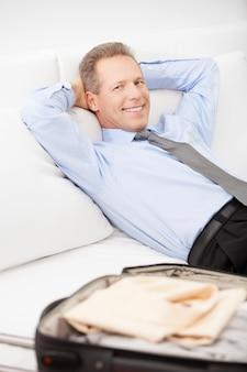 이동 중입니다. 쾌활한 회색 머리 남자 셔츠와 넥타이 침대에 누워 카메라에 미소
