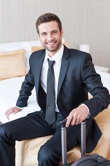 이동 중 경영진. 정장을 입은 자신감 있는 젊은 사업가가 가방을 들고 호텔 방에 있는 침대에 앉아 웃고 있다