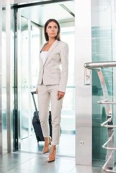 이동 중입니다. 엘리베이터에서 내리는 동안 웃고 있는 가방을 들고 정장을 입은 아름다운 젊은 여성 사업가의 전체 길이