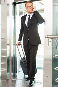 이동 중입니다. 가방을 들고 엘리베이터에서 내리는 동안 휴대전화로 통화하는 정장 차림의 자신감 있는 청년의 전체 길이