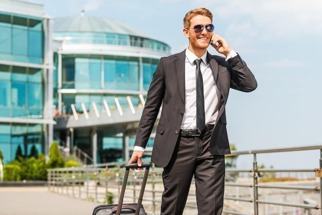 이동 중 경영진. 정장을 입은 잘생긴 젊은 사업가가 가방을 들고 야외에서 걷는 동안 휴대전화로 통화