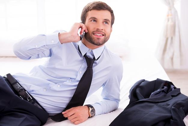 이동 중입니다. 셔츠와 넥타이에 잘 생긴 젊은 남자는 휴대 전화에 얘기 하 고 침대에 누워 있는 동안 웃 고