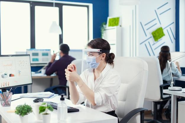 Covid19로 전 세계적으로 유행하는 동안 안면 마스크를 쓴 소독제를 바르고 손을 문지르는 임원. 동료들이 b에서 일하는 동안 소독하는 새로운 일반 직장의 사업가