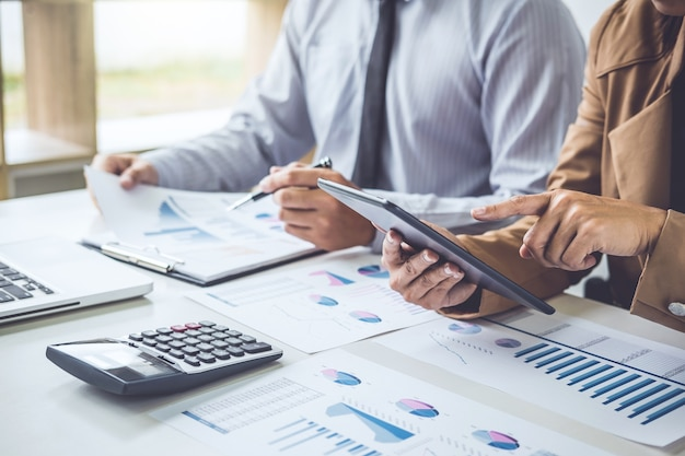 Исполнительная команда обсуждает графики и графики, работающие в бизнес-стратегии и финансовой