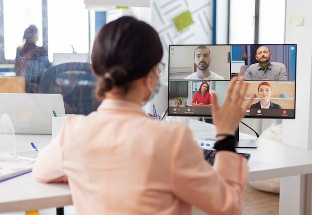 Исполнительная женщина на новом рабочем месте разговаривает по удаленной видеосвязи с командой в маске из-за вспышки коронавирусного гриппа. глядя на экран монитора во время виртуального звонка.