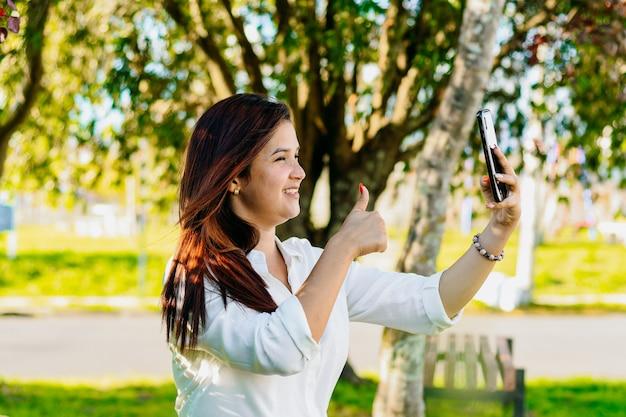 Исполнительная женщина делает видеозвонок, сидя в парке, показывая все хорошо рукой