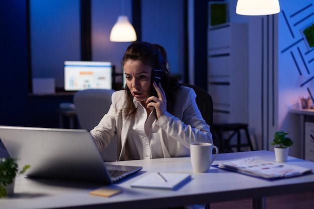 재무 메모를 확인하는 동안 전화로 말하는 중역 여성 관리자