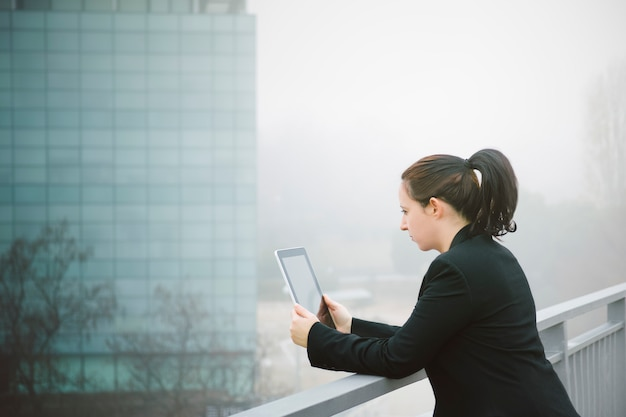 Executive woman reading mail on her tablet supported on a railing with office building i