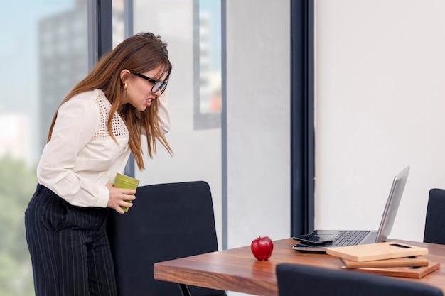 집에서 과로에 지친 중역 여성은 노트북 앞에서 머리에 손을 얹습니다