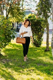 Исполнительная женщина гуляет со своим мобильным телефоном и кошельком в парке