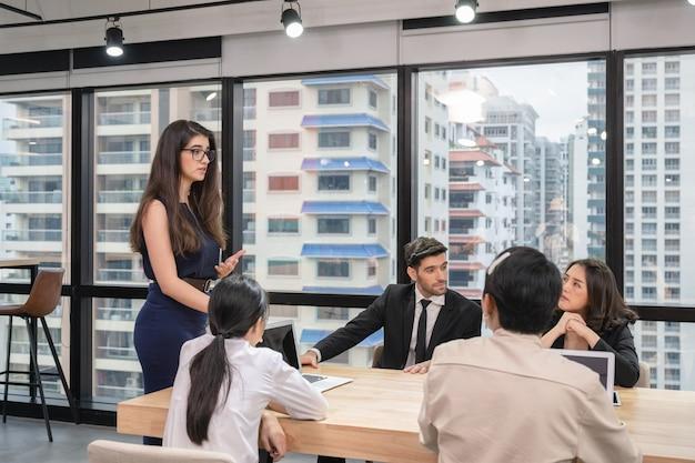 Исполнительная женщина с коллегой, встречающейся по бизнес-плану за столом для переговоров в современном офисе