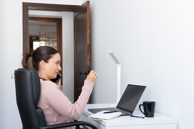 自宅で仕事をし、ノートパソコンを持って机に座って、カメラを見ているエグゼクティブ女性。新しい通常-コピースペース