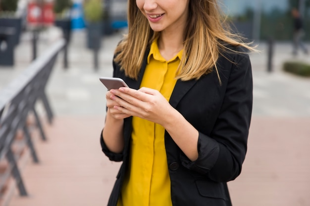 Executive working with a mobile phone in the street with office buildings in the background