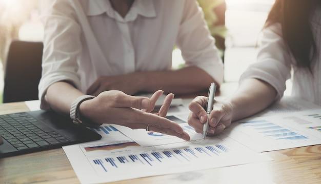 経営幹部と会計士は会社の財務諸表を保持し、それらを一緒に話し合っています。会計士は経営陣との企業財務会議について話し合っています。財務コンセプト。