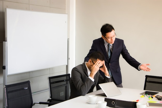 경영진은 감독자에게 직무 오류를 명확히하고 있습니다. 그는 진지한 얼굴을하고 있었고 회의실의 두통처럼 그의 머리에 어두운 머리가 있었다.