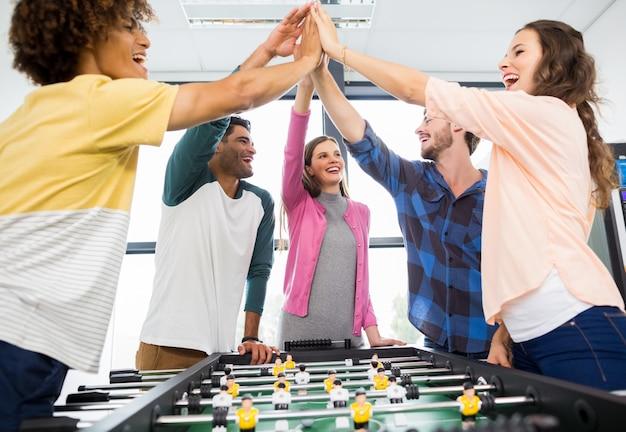 Руководители дают высокие пять, играя в настольный футбол