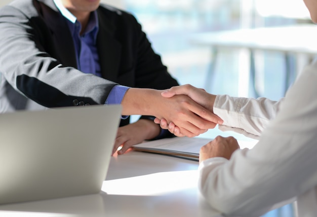 Executives join hands to congratulate the new employee through the interview