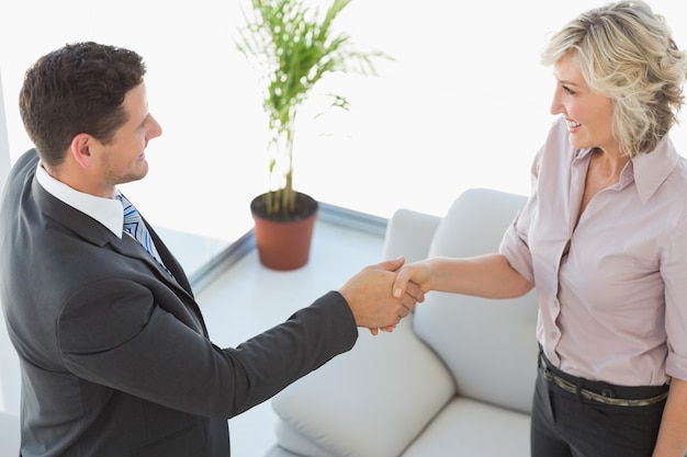 Executives shaking hands in the living room