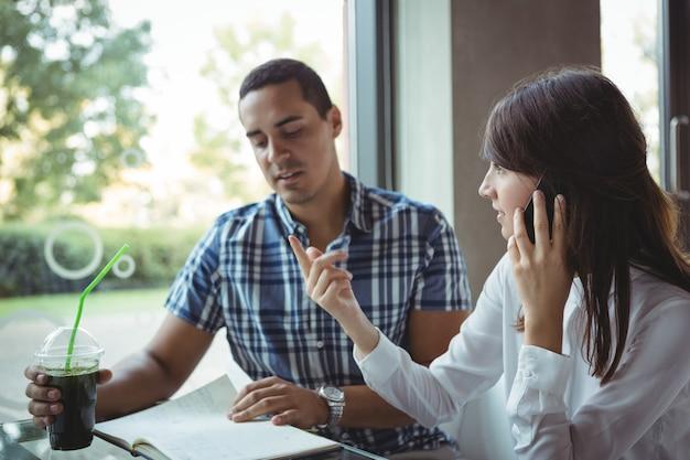 Руководители разговаривают по мобильному телефону во время обсуждения в дневнике