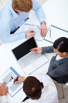 Руководители, работающие вместе на ноутбуке