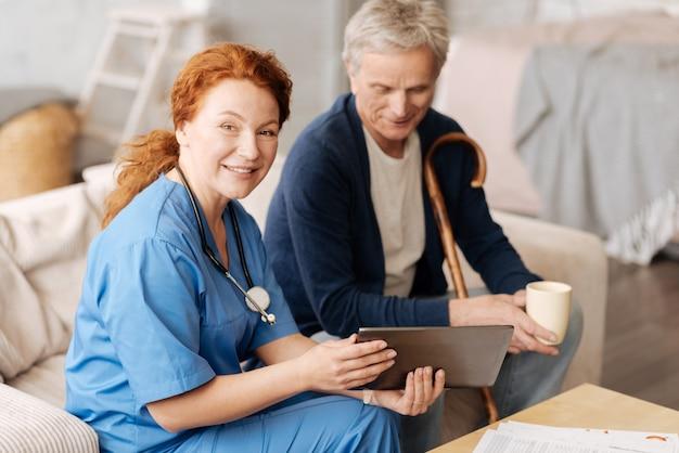 На примере лекции. обученная, мудрая и позитивная женщина рассказывает пациенту все о процессе лечения и использует планшет для иллюстрации своих слов.