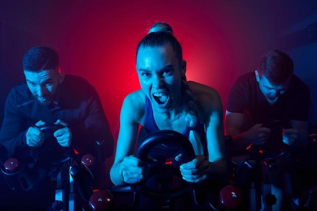 집중 훈련을받은 여성과 친구의 피트니스 체육관에서 운동 자전거 심장 운동, 슬림 바디를위한 에어로빅 기계로 체중 감량, 그들은 비명을 지르고 있습니다.