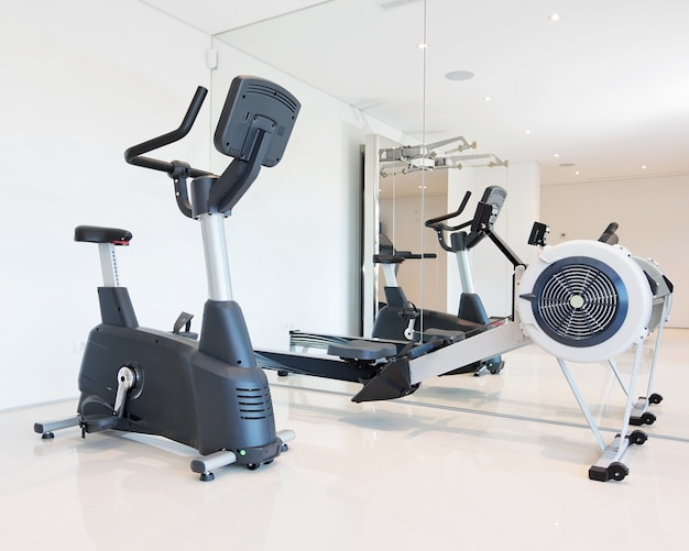 Exercise bike and rowing simulator in the luxury gym close-up.