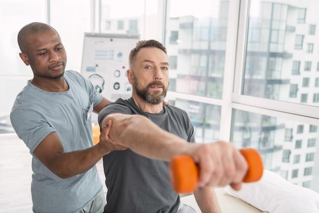 筋肉のための運動。彼の医者に助けられてダンベルを持ち上げるハンサムなひげを生やした男