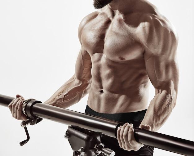 체육관에서 삼두근 운동. 흰색 배경에 격리된 운동하는 매력적인 근육질의 남자.