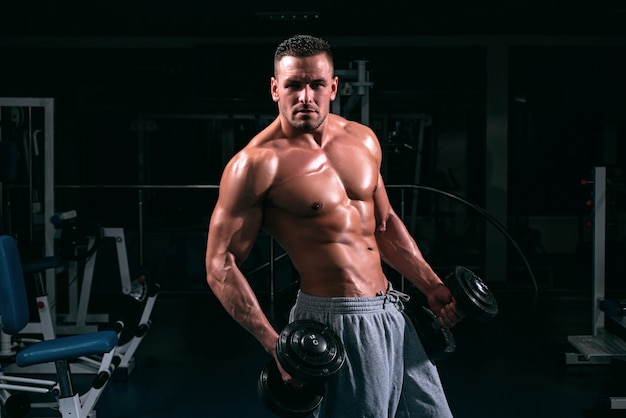 Exercise in gym. sports workout. fitness man in focused on lifting a dumbbell.
