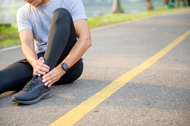 운동 부상 개념 : 젊은 아시아 인 주자가 발목 통증으로 공원 거리에 앉아 아픈 발목을 잡고 심한 통증을 느끼면서 다리를 구부립니다.