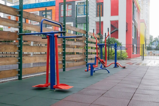 Тренажеры и тренажеры для занятий на открытой спортивной площадке в пасмурную дождливую погоду без людей.