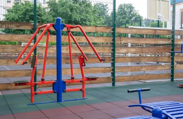 Тренажеры и фитнес-оборудование для занятий на открытой спортивной площадке в пасмурную дождливую погоду без людей.