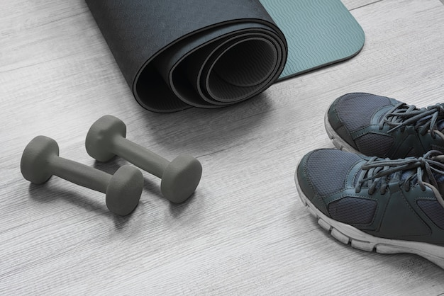 Exercise mat sneakers and dumbbells on the light wooden floor