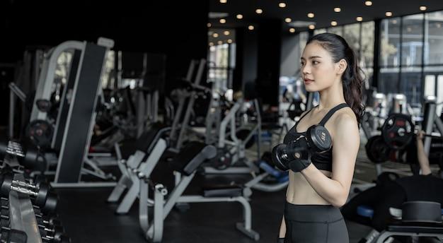 Упражнения азиатских сексуальных женщин с гантелями в тренажерном зале с копией пространства. милая женщина с подъемной гантелью. тайская девушка держит гантель на фоне тренажерного зала. концепция упражнений в тренажерном зале.