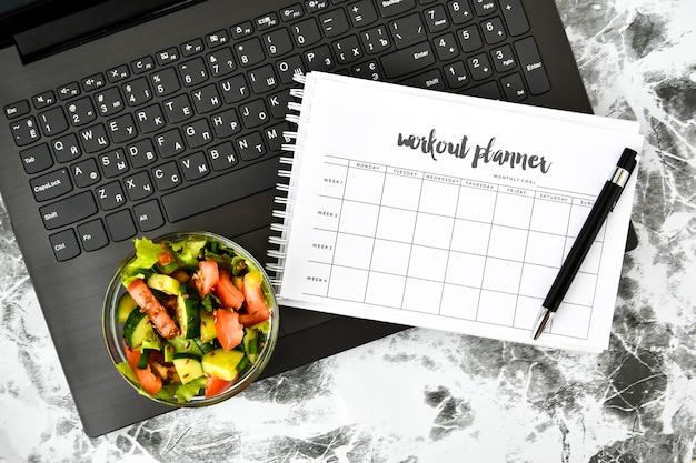 План упражнений на неделю и миска с овощным салатом на рабочем месте возле компьютера