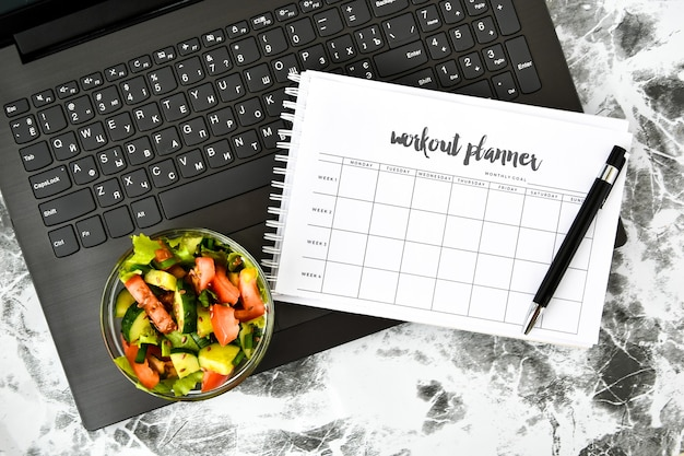 Exercise plan for a week and bowl with vegetable salad in the workplace near the computer