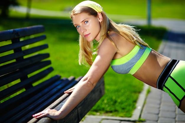 陽気で幸せな笑顔屋外トレーニングトレーニングスポーツフィットネス女性で腕立て伏せを行う運動の女性