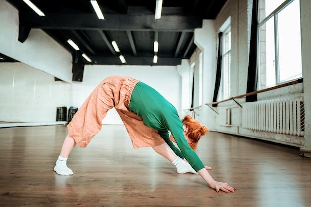 背中のエクササイズ。彼女の背中を伸ばしている緑のタートルネックを身に着けている美しいスリムなヨガのコーチ
