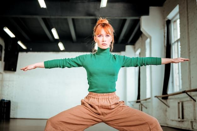足のエクササイズ。強い脚のエクササイズをしている緑のタートルネックを身に着けている格好良いスリムなヨガのコーチ
