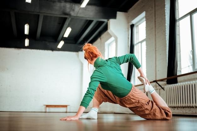 다리 운동. 그녀의 다리를 스트레칭하는 동안 초점을 맞춘 헤어 롤빵을 가진 전문 요가 코치